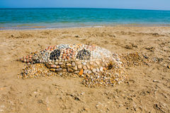 Sea turtle made of sand on the beach, Adriatic Seacoast view. Royalty Free Stock Image