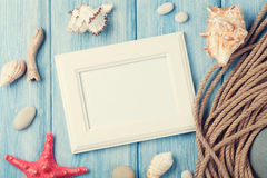 Sea vacation with blank photo frame, star fish and marine rope Stock Photos