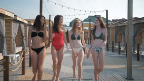 Sea vacations, long-legged girls in swimsuits with beautiful and slender bodies have fun walking along the promenade of