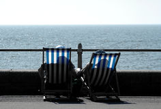 Sea View. Two people on deckchairs, by the Sea, England Stock Image