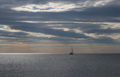 Sea View. Endless sea and a lonely yacht with a narrow beam of sunlight. Plenty of copy space Royalty Free Stock Photos
