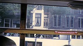 Canals boat tour in 1970s Amsterdam. Sea view of Amsterdam homes architecture and street by boat tour in Holland. Historical archival Amsterdam touristic cruise stock video footage