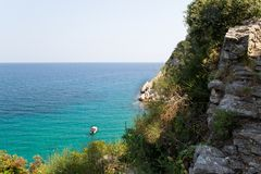 Sea view on one boat in aquamarine water, and piece of cliff, Doumuchari laguna, Greece royalty free stock photo