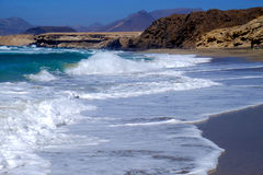 Sea view on the beach La Pared, Fuerteventura, Spain. View on the ocean on the beach La Pared with mixed black and golden sand and with waves moving on the Royalty Free Stock Photo