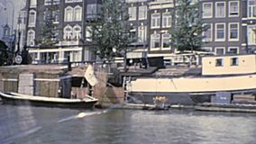 Boat tour Amsterdam in 1970s. Sea view of boats and bridges by river tour in Amsterdam town of Holland. Historical archival touristic cruise in Amsterdam city of stock footage
