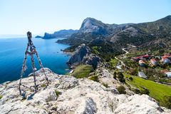 Sea view from the cliff. Rocky cliff above the clear clear Sea and village, View from View Point, Sudak, Crimea stock photo