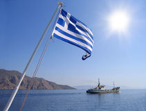 Sea view with greek flag. Mountain, sun and cargo ship stock photography
