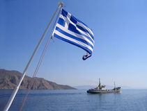 Sea view with greek flag. Mountain and cargo ship stock images