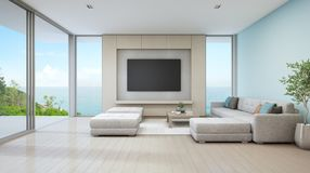 Sea view living room of luxury beach house with glass door and wooden terrace. Large white sofa against blue wall near TV in vacation home or holiday villa for Stock Photo