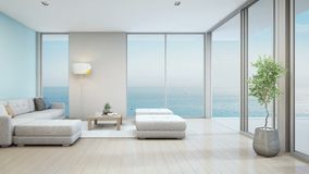 Sea view living room of luxury beach house with indoor plant near glass door and wooden floor deck. Big white sofa against blue wall in vacation home or holiday stock footage
