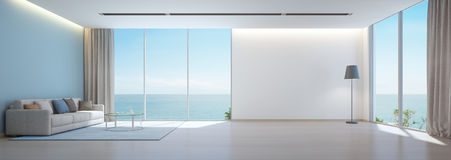 Sea view living room with wooden floor and empty white wall background in luxury beach house, Modern interior of vacation home Royalty Free Stock Photo