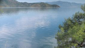 Sea view with pine trees, green hills, islands and clouds reflection in the water. 4k. View of Koycegiz Lake with pine trees, green hills, islands and clouds stock footage