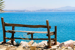 Sea view relaxation bench. Sea view relaxation wooden bench placed at the top and at the very edge of an elevated stone wall Royalty Free Stock Photography