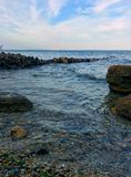 Seascape from rocky coast. Sea view from rocky coast with waves and cloudy sky Stock Image