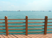 Sea view with ships. View of the sea - A view out to a sunny blue and green sea beside some wooden railings on a seaside wood deck. Expanse of sea, sky and stock photography