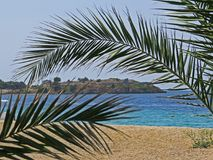 Sea view from the shore towards a fortress in Sithonia peninsula, Halkidiki, with a palm tree leaf close up in front. Travel holiday photo stock photo