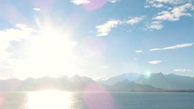 Sea View And Sky Timelapse. Sea view at sun rays on the mountains background. stock video footage