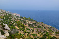 Sea view from steep bank, Malta. Sea view from the steep bank with some agricultural areas, not far seen a small rocky island, the sea is calm and the fog Royalty Free Stock Photos