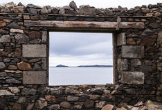 Sea view from a stone window of an old ruin near the ocean Stock Image