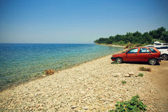 Sea view on summer travel vacation to the coast. Car parking on a beach. Royalty Free Stock Images