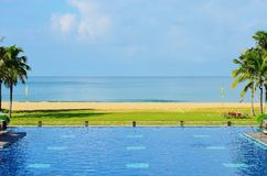 Sea view, a swimming pool and the beach. At sunset Royalty Free Stock Image