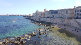 Sea view in Syracuse and coast of Island of Ortigia. Sea view in Syracuse and a glimpse of the promenade on the raised seafront, with volcanic rocks coming out Stock Images