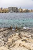 View to St. Julian`s with part of the limestone shore and metal beach ladder in the foreground, St. Julian`s Malta. Sea view to St. Julian`s with part of the Stock Image