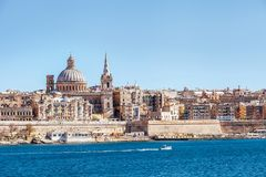 Sea view of Valletta city - the capital of Malta with Basilica o. Valletta, Malta - March 30, 2018: Sea view of Valletta city - the capital of Malta with Royalty Free Stock Images