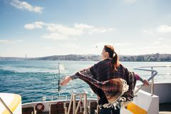 Sea voyage to Bosporus Strait on a sunny day. Happy female traveler on a ferry enjoying panorama view of Istanbul on a sunny day Stock Images
