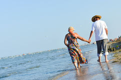 Sea walk & happy mature couple at seashore sandy beach and holding hands Royalty Free Stock Photo