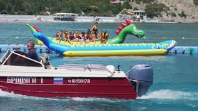 Russia, Crimea, 6 july 2017. Sea walk tourists holiday makers vacationers on an inflatable banana boat with a water. Sea walk - tourists holidaymakers stock video
