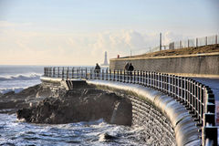 Sea Wall at Seaburn. The sea wall at Seaburn, Sunderland upon the River Wear.  Roker Lighthouse can be seen in the distance Royalty Free Stock Photography