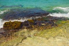 The sea washing over algae-covered rocks Royalty Free Stock Photo