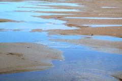 Sea water on the beach at ebb-tide. Small lake close to the ocean or sea Stock Photo