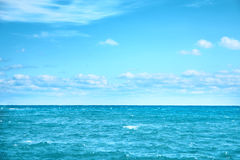 Sea water and blue sky with white clouds Stock Photos
