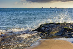 Sea water breaking over the stones. With islands and horizon in background Stock Photos