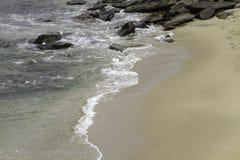 Sea Water Breaking on Rock Formations. Gentle waves breaking on sand beach Royalty Free Stock Image