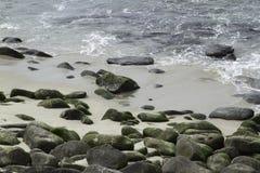 Sea Water Breaking on Rock Formations. Ocean rocks embedded on sandy beach as the tide recedes Royalty Free Stock Image