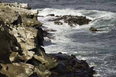 Sea Water Breaking on Rock Formations. Ocean waves hitting coastal rocks and cliffs Stock Image