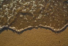 Sea water on brown sand royalty free stock image