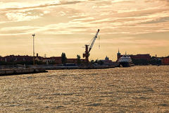 Sea water and buildings in the morning. Venice, Italy. Sea water, buildings and port cranes in the morning. Venice, Italy Royalty Free Stock Photo