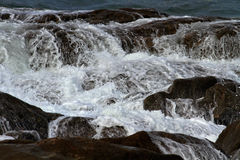 Sea water flowing over rocks Stock Image