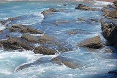 SEA WATER AND FOAM BETWEEN ROCKS Stock Image