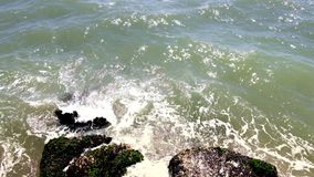Sea water hitting rocks on the shore. stock video footage