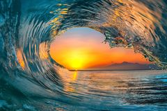 Sea water ocean wave surfing water surface. Colorful vibrant Sunset Sea water ocean wave in barrel shape for surfing royalty free stock images
