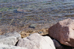 Sea water and rocks. Background of still sea water and rocks texture Stock Image