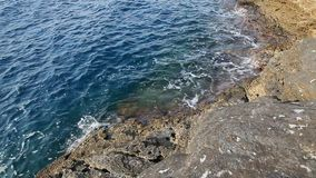Sea water and rocks in Thassos island, Greece, next to the natural pool called Giola. Sound of waves and wind stock footage