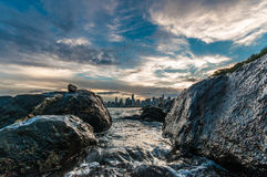 Sea water between rocks (2). The sea water between two rocks on the beach. On the background, the city of Balneario Camboriu Stock Photography
