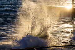 The sea water splashes in the rays of the setting sun Royalty Free Stock Photography