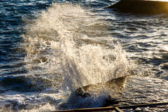 The sea water splashes in the rays of the setting sun Royalty Free Stock Images